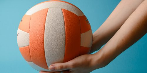 Woman hold volleyball in her hands. Blue background